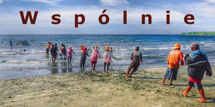 grupa ludzi wspólnie pracuje wyciągając linę z morza