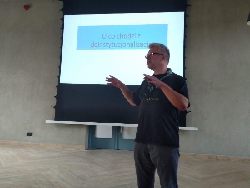 """Mężczyzna (Cezary Miżejewski) z podniesionymi rekami mówi na tle wyświetlonego slajdu z napisem """"O co chodzi z deinstytucjonalizacją?"""""""
