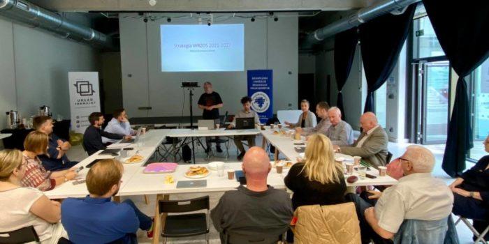 Spotkanie dotyczące strategii WRZOS w latach 2021-20217. Kilkanaście osób wokół stołu. Prezentuje stojący mężczyzna, cezary Miżejewski, prezes WRZOS